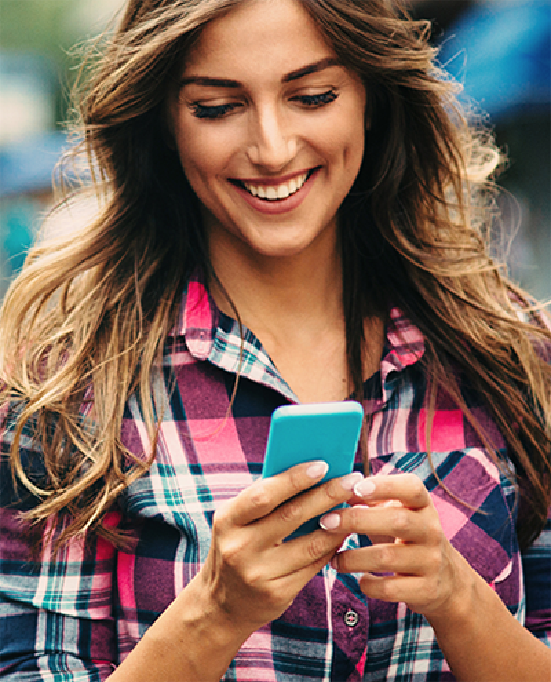A young woman looking at her smartphone and smiling